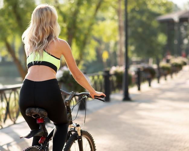 Mulher andando de bicicleta por trás da foto Foto Premium