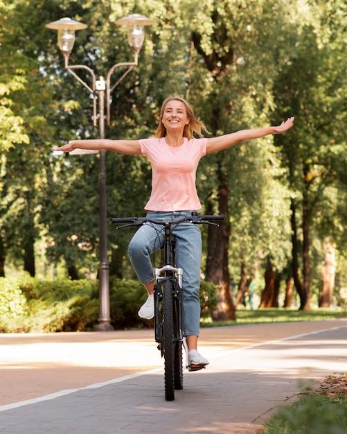 Mulher andando de bicicleta sem segurá-la Foto gratuita