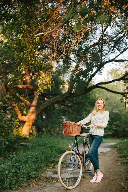 Mulher andando de bicicleta vintage com cesta Foto Premium