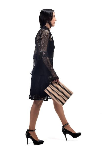 Mulher andando e com um vestido e sapatos de salto isolados no fundo branco Foto Premium