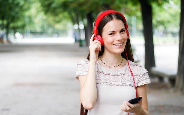 Mulher andando em um parque enquanto estiver usando seu smartphone para ouvir música Foto Premium