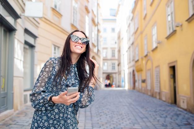 Mulher andando na cidade. jovem atrativos turísticos ao ar livre na cidade europeia Foto Premium