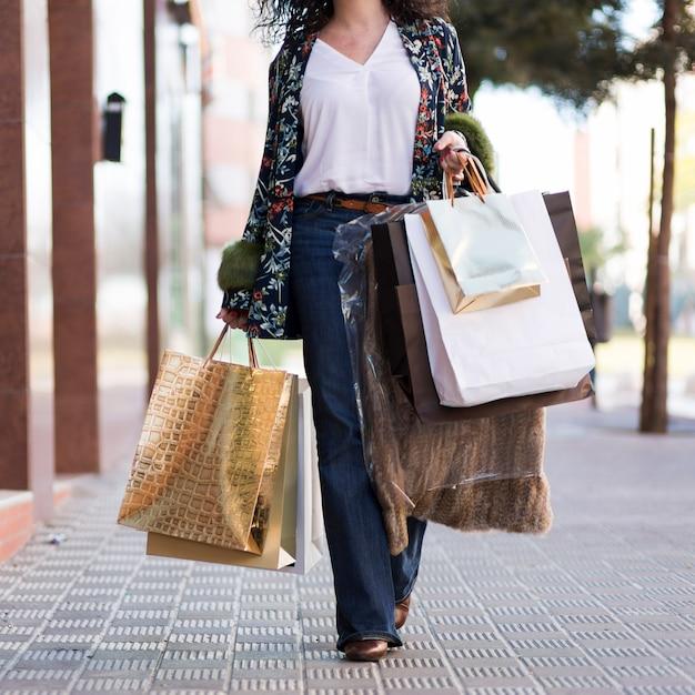 Mulher andando na rua com sacos de compras Foto gratuita
