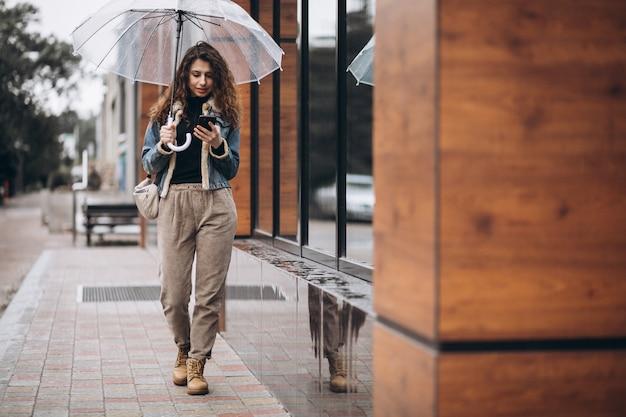 Mulher andando sob o guarda-chuva em um tempo chuvoso Foto gratuita