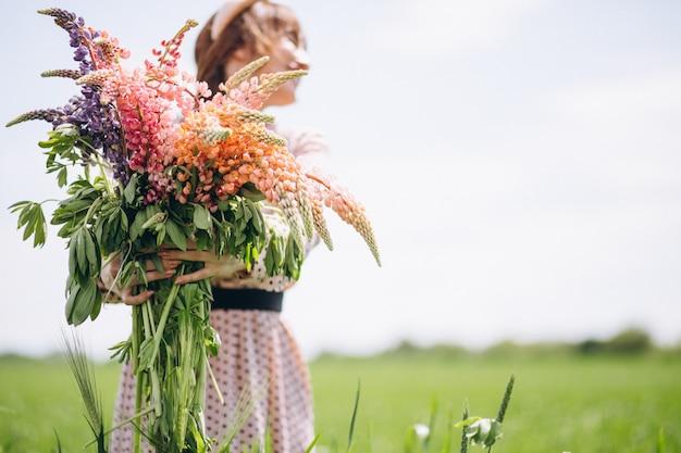 Mulher, andar, em, um, campo, com, lupinuses Foto gratuita
