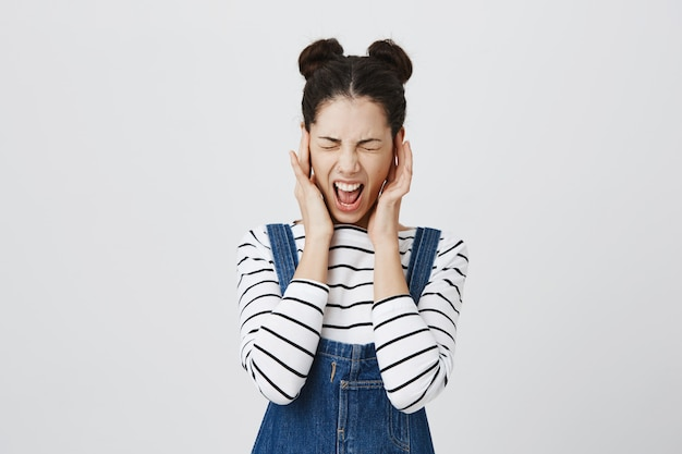 Mulher angustiada fecha os ouvidos e grita Foto gratuita