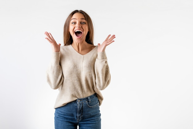 Mulher animada feliz pulando com um grande sorriso isolado sobre o branco Foto Premium