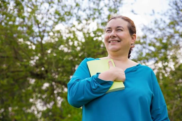 Mulher animada sorridente impressionado com a história do livro Foto gratuita
