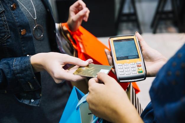 Mulher anônima pagando na loja Foto gratuita