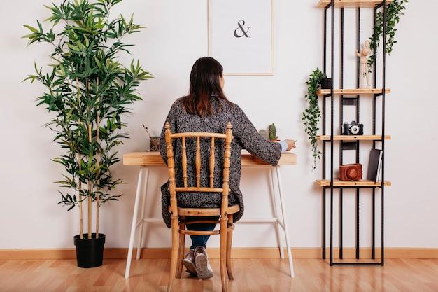 Mulher anônima que estuda no quarto moderno Foto gratuita