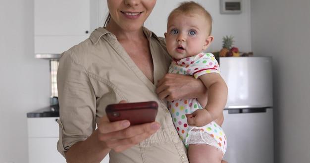 Mulher anônima sorrindo e navegando smartphone enquanto de pé na cozinha e segurando doce bebê Foto Premium