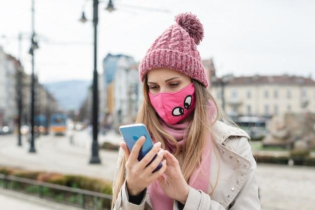 Mulher ansiosa usando máscara de coroa, verificando notícias em seu telefone Foto Premium