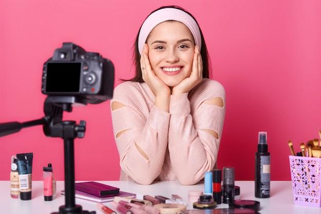 Mulher anuncia novos produtos de beleza, faz vídeo seu blog. beleza vlogger senta sorrindo na frente da câmera Foto Premium