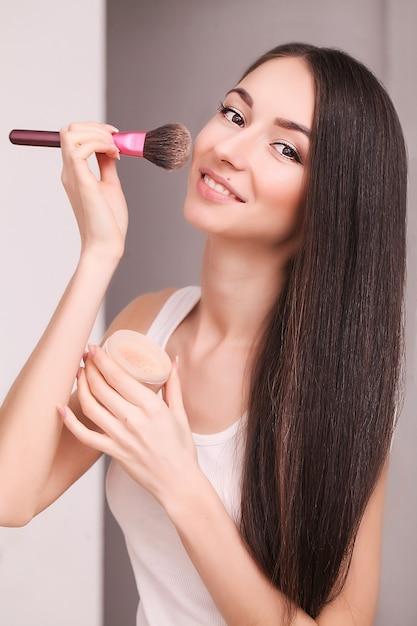 Mulher aplica maquiagem no rosto com um pincel Foto Premium