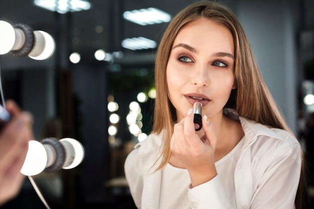 Mulher, aplicando batom, olhar espelho Foto gratuita