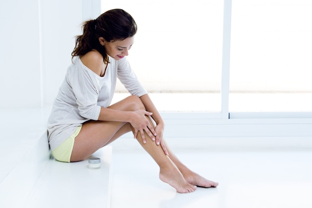 Mulher aplicando creme nas pernas Foto gratuita