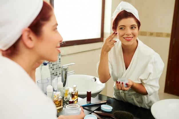 Mulher aplicando creme nutritivo para o rosto Foto Premium