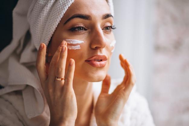 Mulher, aplicando, creme rosto Foto gratuita