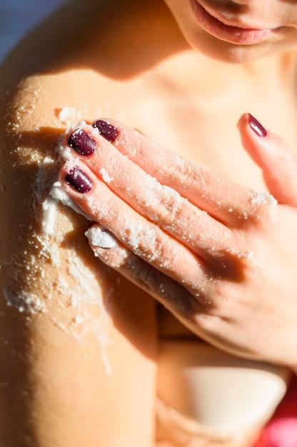 Mulher aplicando esfoliação corporal no ombro Foto gratuita
