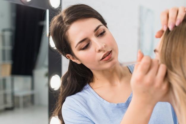 Mulher, aplicando, eyeliner, escova, fazer, olho, maquilagem Foto gratuita
