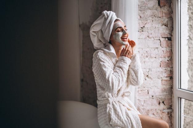 Mulher, aplicando, facial, maskin, banheiro Foto gratuita