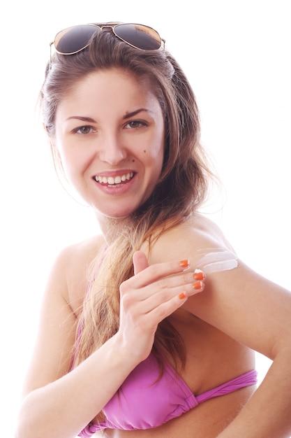 Mulher aplicar creme de proteção solar Foto gratuita