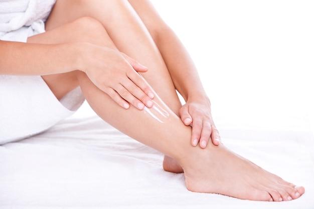 Mulher aplicar creme hidratante nas pernas Foto gratuita
