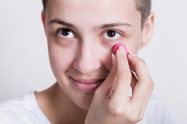 Mulher aplicar creme para olheiras Foto gratuita