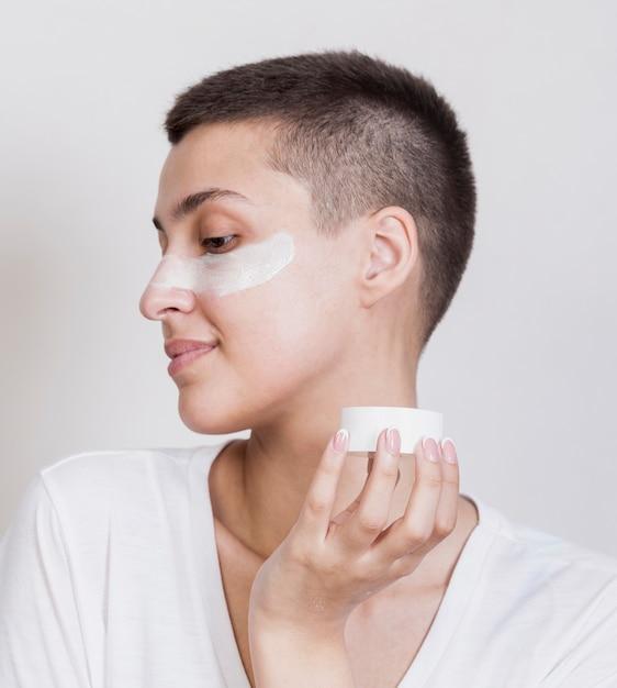 Mulher aplicar creme para os cuidados com a pele no rosto Foto gratuita