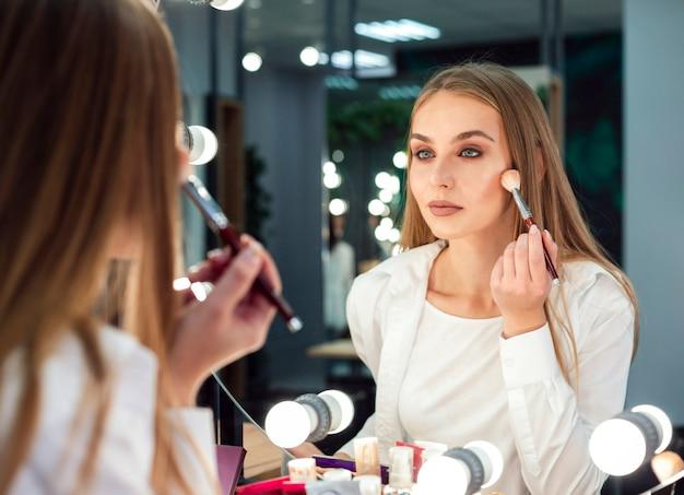 Mulher aplicar pó no espelho Foto gratuita