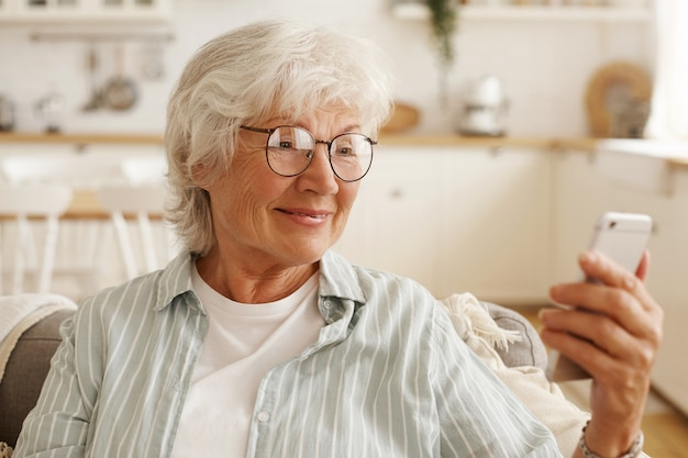 Mulher aposentada feliz e alegre de óculos redondos navegando na internet no celular, olhando para a tela do celular com um largo sorriso, reservando passagens aéreas, planejando viagem ou rolando fotos via rede social Foto gratuita