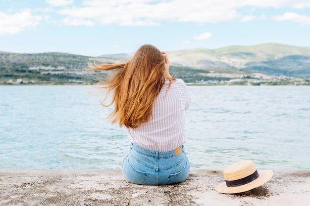 Mulher, apreciando a vista do oceano com montanhas Foto gratuita