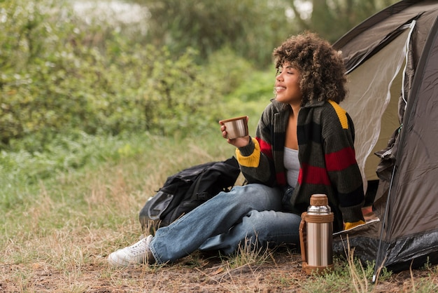 Mulher apreciando a vista enquanto acampa ao ar livre Foto gratuita