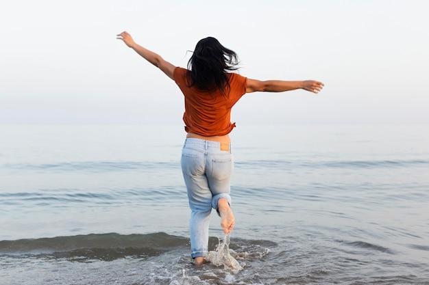 Mulher, apreciando o mar na praia Foto gratuita