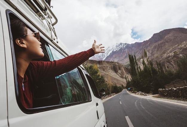 Mulher, aproveitando a brisa fresca da janela do carro Foto Premium