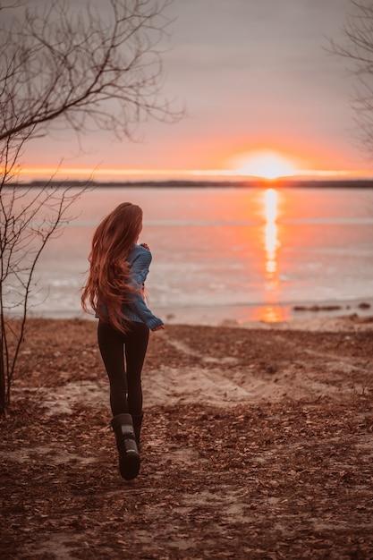 Mulher, aproveitando o tempo relaxante no lago bonito ao nascer do sol Foto gratuita