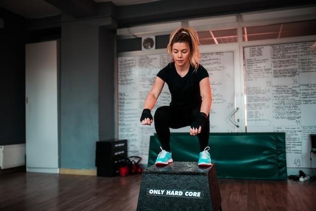 Mulher apta do louro que salta no bloco na ginástica. Foto Premium