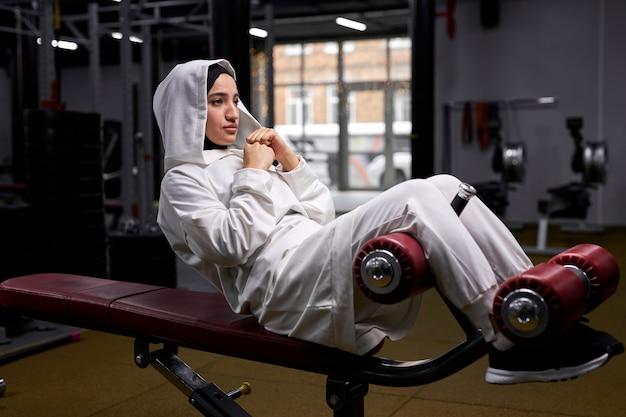 Mulher árabe bombeia abdominais no centro de fitness, deitada no equipamento levantando o corpo, concentrada no treino, sozinha. conceito de esporte e crossfit Foto Premium