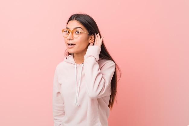 Mulher árabe bonita nova que veste um olhar ocasional do esporte que tenta escutar uma bisbolhetice. Foto Premium