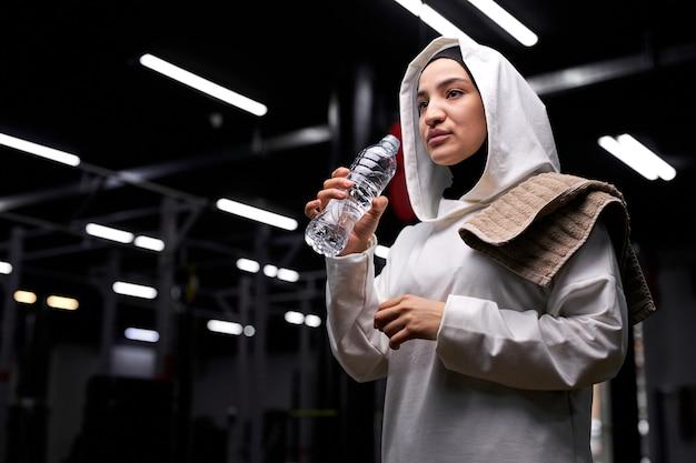 Mulher árabe de hijab vai tomar um gole d'água durante o treino na academia, fazer uma pausa, descansar, usando hijab esportivo branco Foto Premium