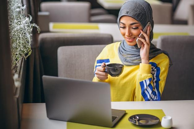 Mulher árabe em hijab dentro de um café trabalhando no laptop Foto gratuita