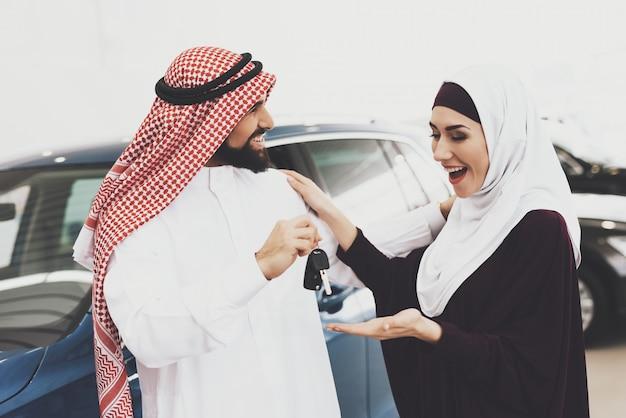 Mulher árabe muito feliz tem as chaves do carro do homem amoroso. Foto Premium