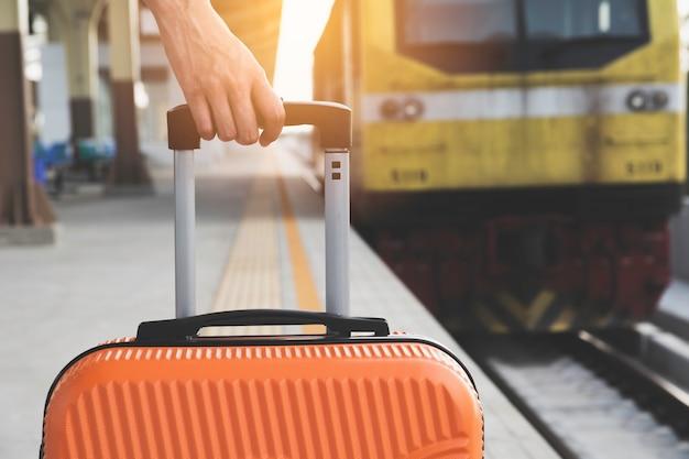 Mulher arrastando mala laranja bagagem saco, andando na estação de trem. Foto Premium