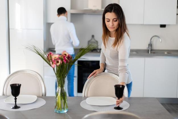 Mulher arrumando a mesa enquanto o namorado está cozinhando Foto Premium