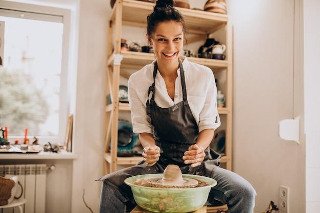 Mulher artesã em uma loja de cerâmica Foto gratuita