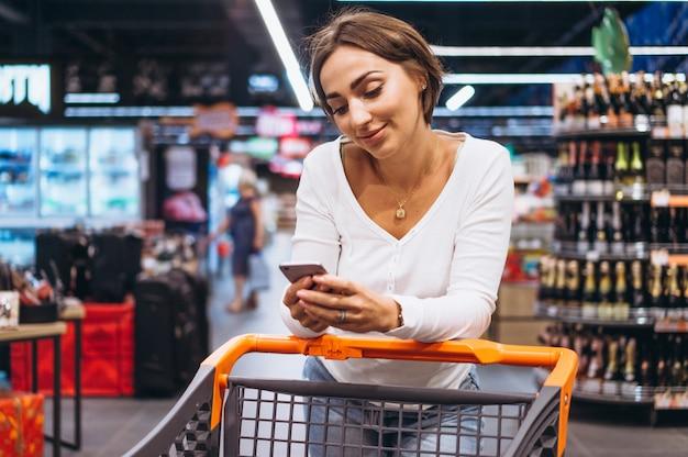 Mulher às compras no supermercado e falando no telefone Foto gratuita