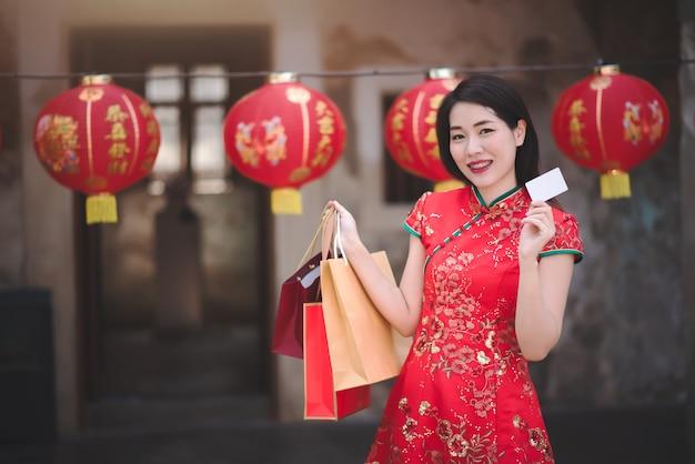 Mulher asian, em, cheongsam, vestido vermelho, segurando, bolsa para compras, e, crédito, em, chinês, ano novo Foto Premium