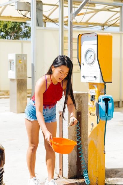 Mulher asian, obtendo água, em, tigela, em, posto gasolina Foto gratuita
