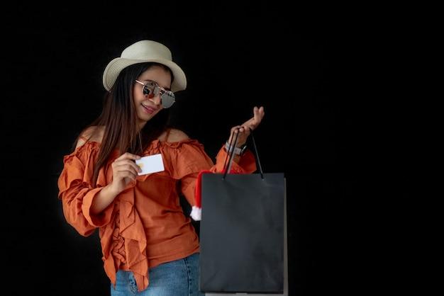 Mulher asian, segurando, cartão crédito, com, pretas, sexta feira, saco de compras, e, papai noel, chapéu Foto Premium