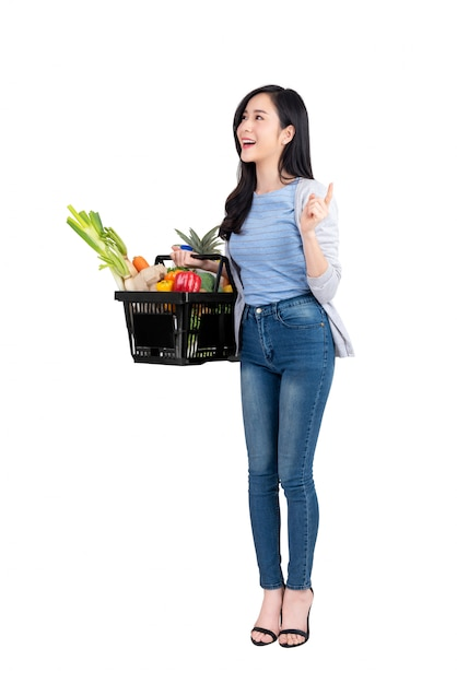 Mulher asian, segurando, cesta shopping, cheio, de, legumes, e, mantimentos Foto Premium